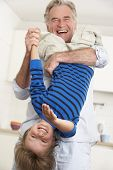pic of upside  - Grandfather Holding Grandson Upside Down At Home - JPG