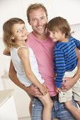 stock photo of cuddle  - Father Giving Children Cuddle At Home - JPG