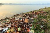 stock photo of polluted  - Rubbish pollution with plastic and other packaging stuffs on the bank of the Taungthaman lake near U Bein bridge in Myanmar  - JPG