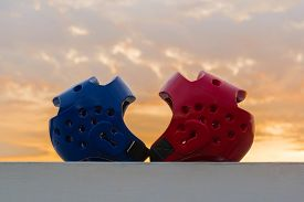 stock photo of taekwondo  - Red and Blue Taekwondo head guard with on sunset background.