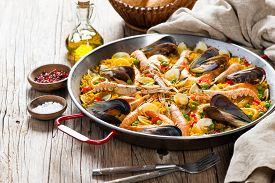 stock photo of traditional  - Traditional seafood paella in the fry pan on a wooden old table - JPG