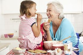 stock photo of grandmother  - Grandmother And Granddaughter Baking In Kitchen - JPG