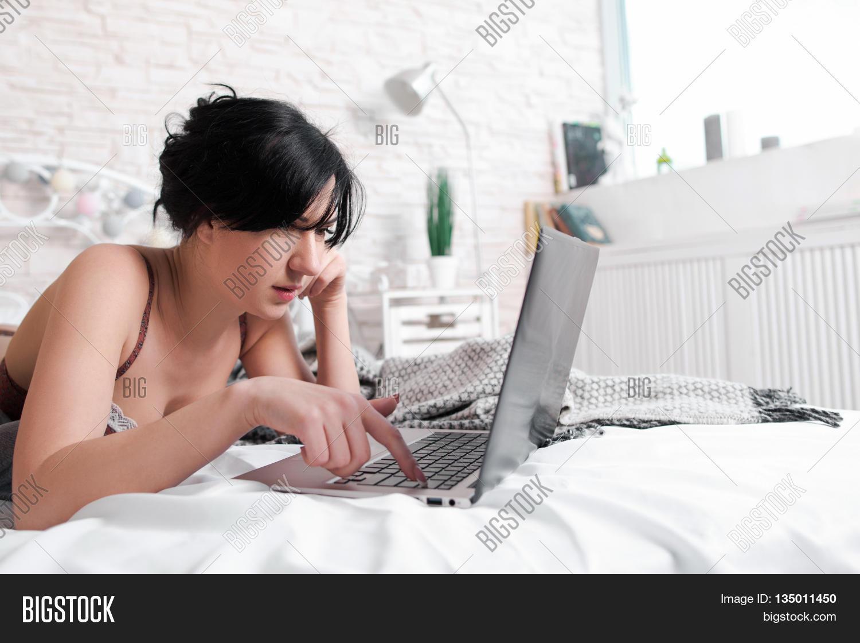 girl naked looking at laptop computer