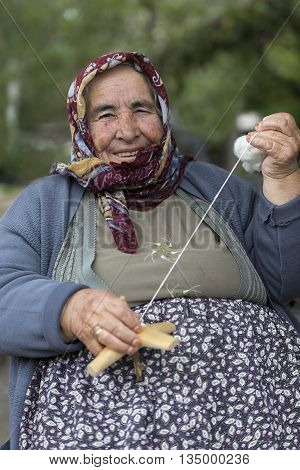 Elderly woman spinning the cotton and smiling.