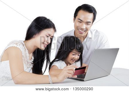 Happy family using credit card and notebook computer for shopping online on the table isolated on white background