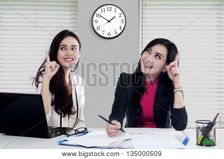 Two female workers get smart idea while working together with laptop and documents on the desk in office