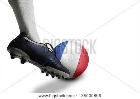 Close up of foot of football player kicking a ball with national flag of France isolated over white background