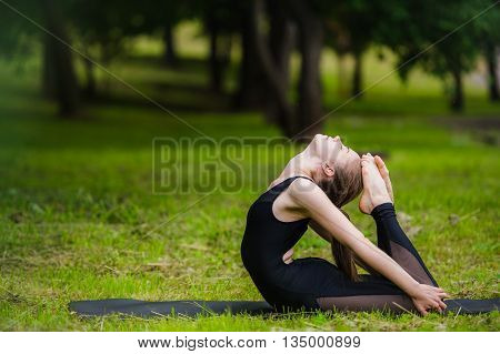 Young woman doing gymnastics yoga and stretching in the city park on sunset.