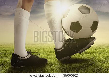 Image of foot of football player doing exercise and a trick with a ball at the field