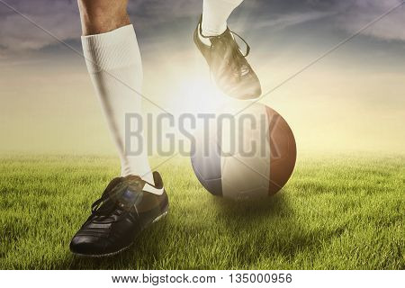 Close up of the foot of football player with a ball and national flag of France on the field