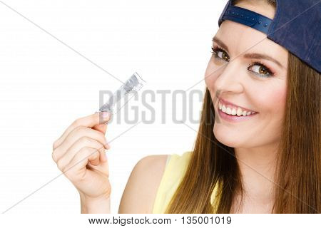 Funky people concept. Young woman with chewing gum. Bubble gum is in the silver paper. Girl is wearing cap and yellow shirt.