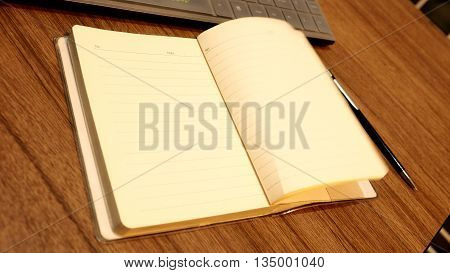 Note Book Open pencil and key board on wood desk background blur.