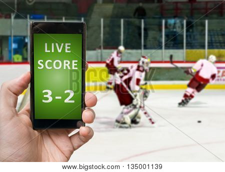 Man Is Watching Ice Hockey And Holds Smartphone In Hand With Liv