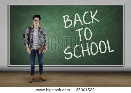 Male high school student standing in the classroom with text of Back To School on the blackboard