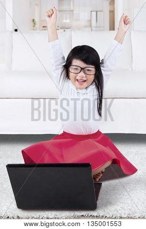 Happy little girl sitting on the carpet at home while smiling and raising hands with laptop computer