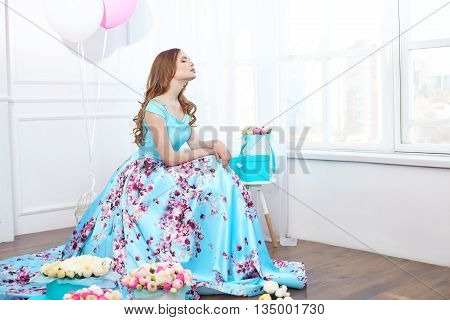 Beautiful young girl in a blue dress sitting in a bright interior with large windows placed around the box with a bouquet of flowers on a background of bright balls.