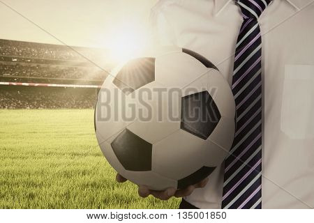 Close up of a man holding a soccer ball while wearing formal suit at the field