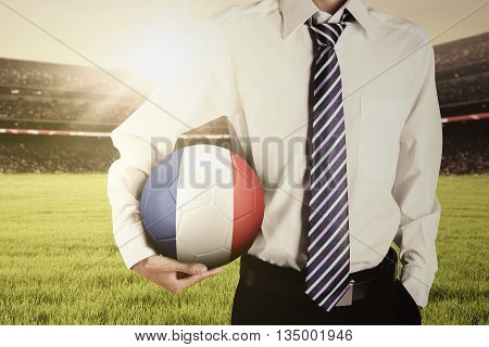 Businessperson wearing formal suit at the field while holding a soccer ball with flag of France