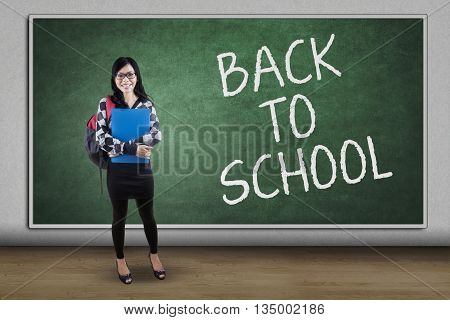 Portrait of a pretty high school student standing in the classroom with text of Back to School on the chalkboard