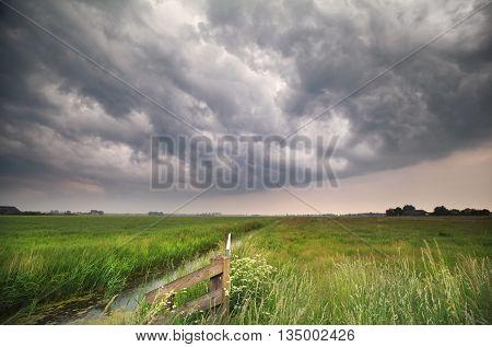 dark stormy clouds over green meadow Groningen Netherlands