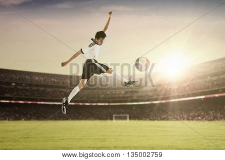 Photo of a soccer player leaps on the field while kicking a ball with national flag of France