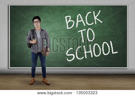 Full length of male teenage student carrying bag and book while standing in the class with text of Back to School on the blackboard