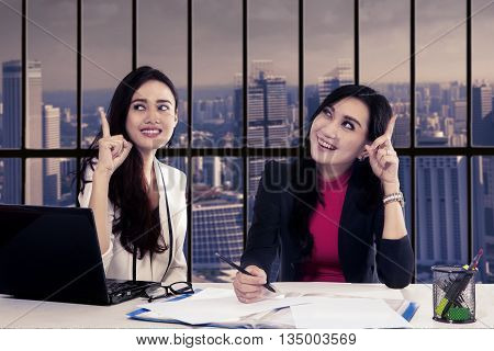Two beautiful businesswoman get good idea while working together in the office