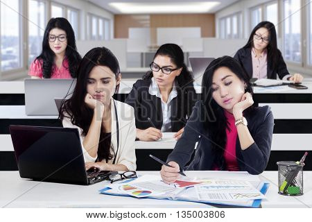 Two female worker leaning head on hand looking tired and other employee busy working on the desk in office
