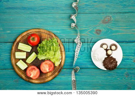 Choice Of Food: Diet On Vegetables Or Cake And Candy. And Centimeter Tape