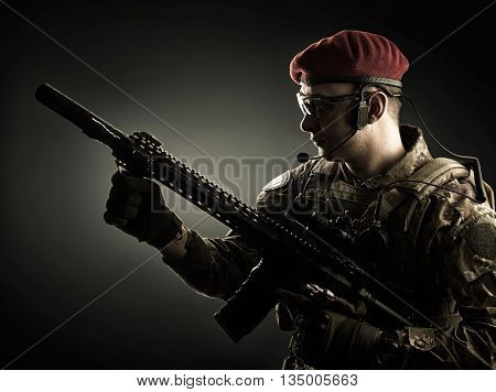 silhouette of Young handsome military man in italian camouflage holding automatic rifle he wearing red beret and gloves