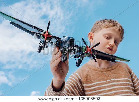 Boy play with toy plane with blue sky background.