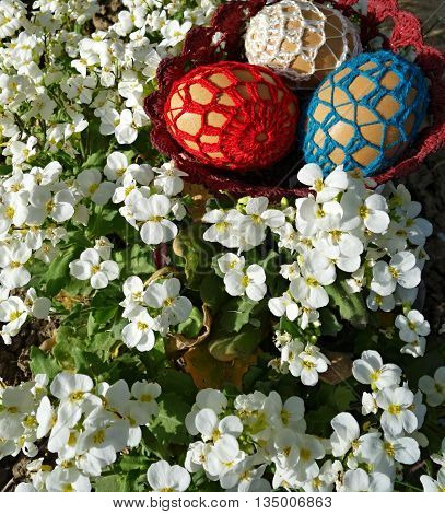 Easter eggs in a basket on a flower