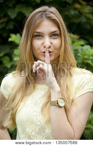 Young beautiful blonde woman has put forefinger to lips as sign of silence, against green summer park