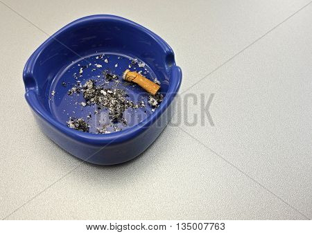 smoking a cigarette in a blue ashtray on gray background