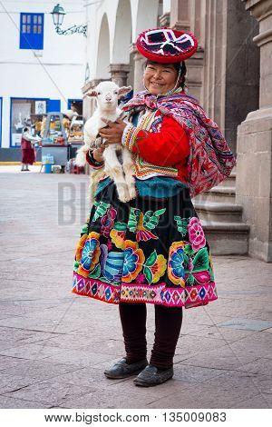 Cuzco Peru - March 18 2015: Peruvian woman in traditional dresses pose for tourists in Cuzco Peru