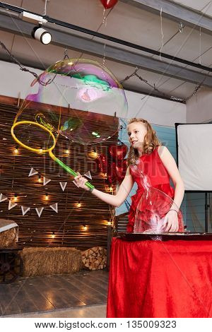 Girl in a red dress makes Girl in a red dress makes big soap bubbles on holiday on holiday