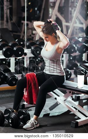 Womans break in workout to tie her hair. Female athlete tying hair before her workout with dumbbells. Beautiful brunette sitting at gym with red towel on her leg and tying her hair.