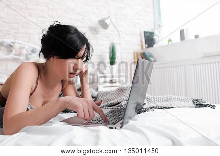 Nude brunette working on laptop close-up. Head and shoulders of pretty brunette woman, lying on bed in undies and working on laptop. Lying on bed brunette in lingerie with computer