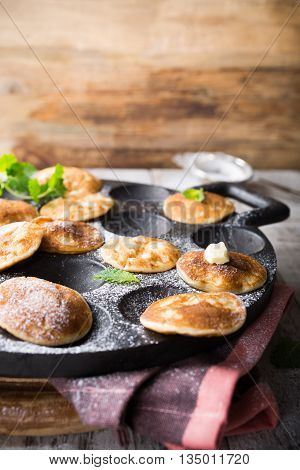 Homemade dutch mini pancakes called poffertjes with mint on special pan with grooves. Healthy food concept with copy space.