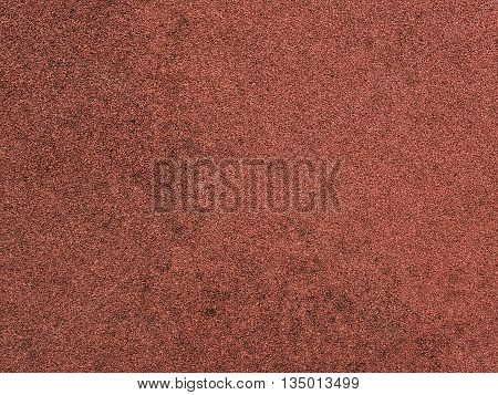 Red protective rubber coating for sports and children playgrounds. Close up. Texture background