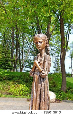 UKRAINE, KYIV - MAY 01, 2013: Hungry girl bronze monument and Monument to Victims of Famine devoted to genocide victims of the Ukrainian people of 1932-1933 years, Kyiv, Ukraine