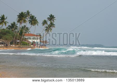 HIKKADUWA, SRI LANKA - MARCH 22, 2015: Evening surf on the beach Hikkaduwa. Famous, tourist beach Sri Lanka