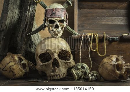 closeup pirate skull with two swords over on human skull pile awesome and treasure coffer background still life style pirate concept for halloween