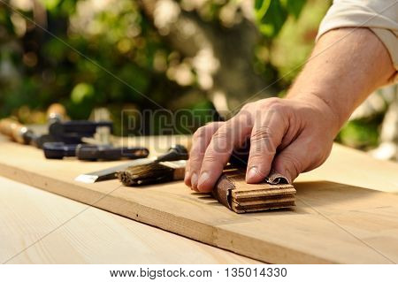 Carpenter hands grinding wooden board and work tools background