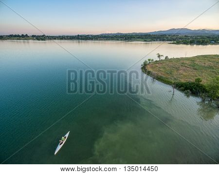 aerial view of a lake with canoe, summer evening in Colorado with Rocky Mountains in background