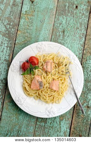 Portion of spaghetti with basil tomatoes and red fish on old wooden table vertical