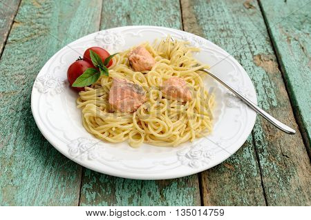 Portion of spaghetti with basil tomatoes and red fish filet on old wooden table horizontal