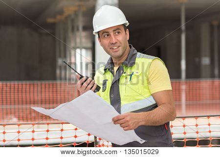 Civil Engineer at construction site is inspecting ongoing production according to design drawings.