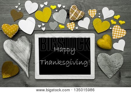 Chalkboard With English Text Happy Thanksgiving. Many Yellow Textile Hearts. Grey Wooden Background With Vintage, Rustic Or Retro Style. Black And White Style With Colored Hot Spots