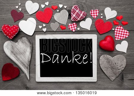 Chalkboard With German Text Danke Means Thank You. Red Textile Hearts. Grey Wooden Background With Vintage, Or Retro Style. Black And White Style With Colored Hot Spots